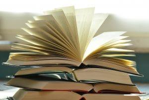 5 Bücher auf einem Stapel. Das oberste ist aufgeschlagen und flattert im Wind.