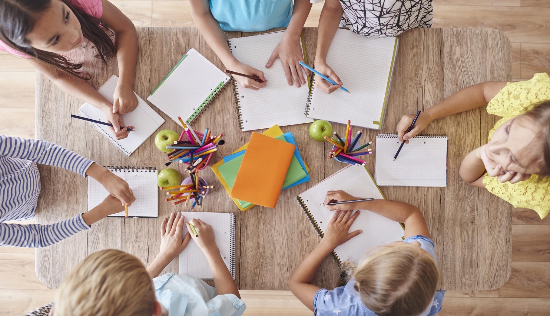 Kinder sitzen am Tisch und Lernen in einer Lerngruppe