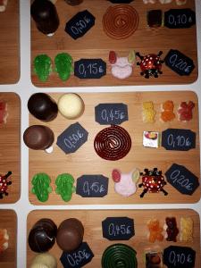 Holzbrett mit diversen Süßigkeiten und Preistafeln zum Umgang mit Geld