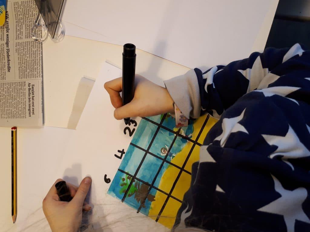 Ein Kind zeichnet ein Raster auf dem Bild.