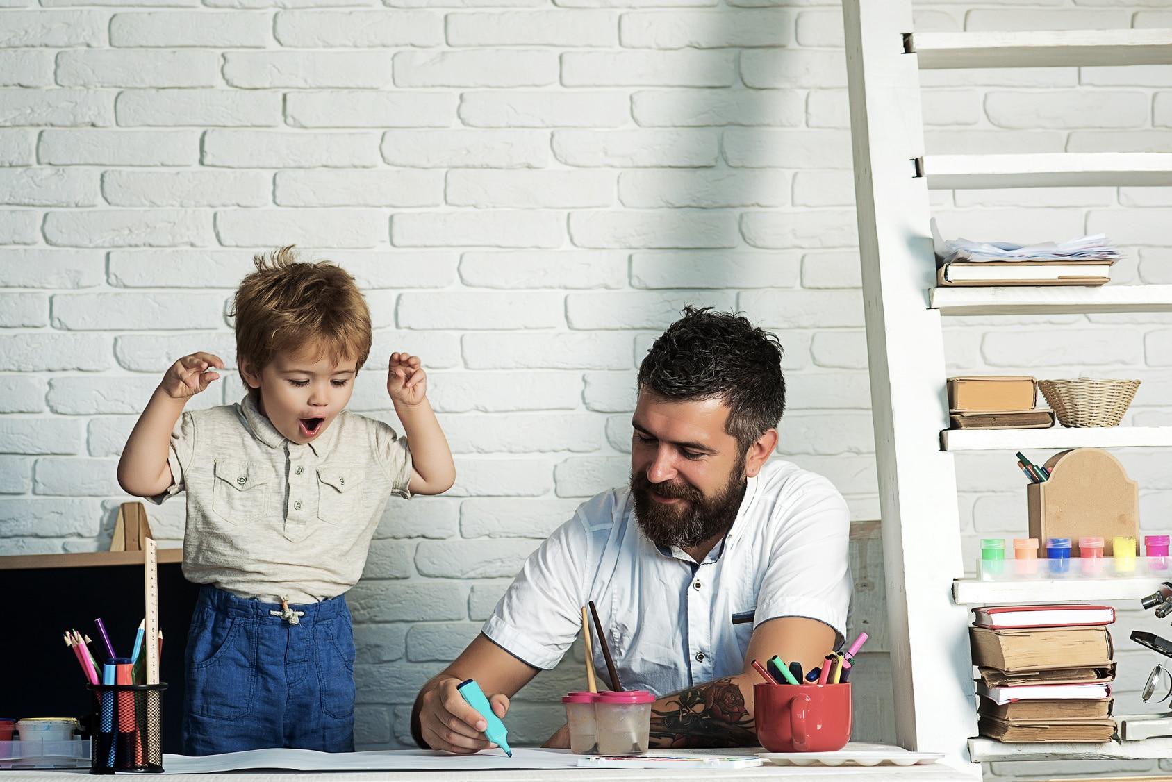 Vater lernt mit Kind und Grundschulkind hat Spaß