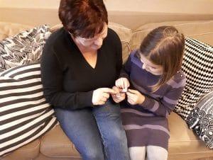 Oma und Mädchen sitzen auf dem Sofa und vergleichen ihre Armbanduhren Lerntrick Uhr lernen