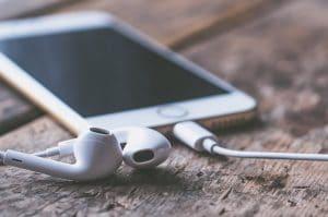 Weißes Handy mit Kopfhörern auf Holztisch