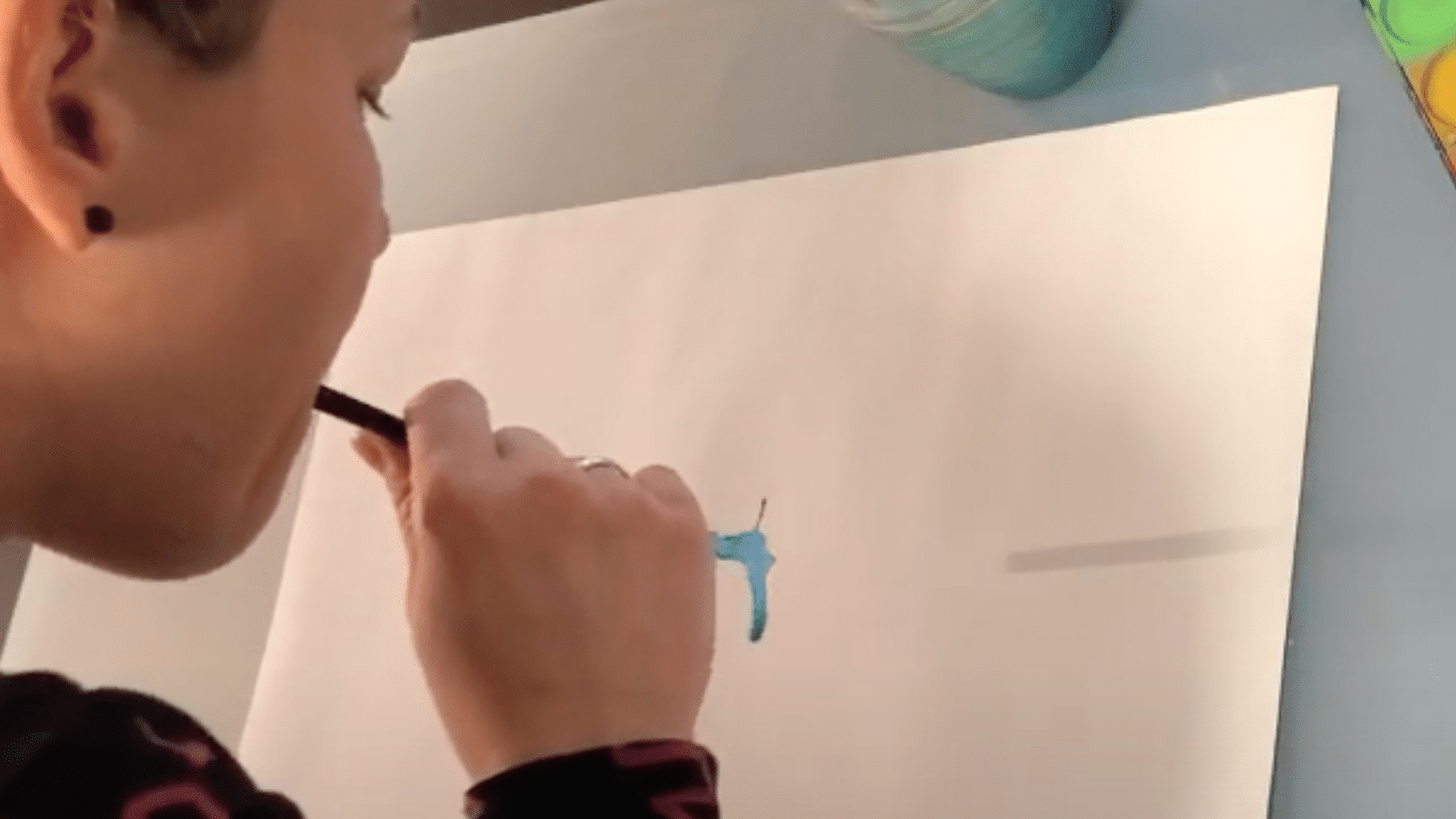 Mit dem Strohhalm verteilst du Farbe auf dem Blatt Papier